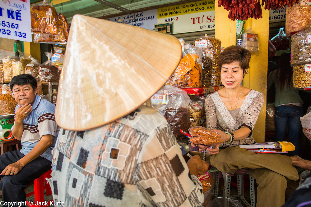 "12 APRIL 2012 - HO CHI MINH CITY, VIETNAM:  A woman wearing a traditional Vietnamese conical hat completes a purchase from a vendor in Binh Tay Market. Binh Tay market is the largest market in Ho Chi Minh City and is the central market of Cholon. Cholon is the Chinese-influenced section of Ho Chi Minh City (former Saigon). It is the largest ""Chinatown"" in Vietnam. Cholon consists of the western half of District 5 as well as several adjoining neighborhoods in District 6. The Vietnamese name Cholon literally means ""big"" (lon) ""market"" (cho). Incorporated in 1879 as a city 11 km from central Saigon. By the 1930s, it had expanded to the city limit of Saigon. On April 27, 1931, French colonial authorities merged the two cities to form Saigon-Cholon. In 1956, ""Cholon"" was dropped from the name and the city became known as Saigon. During the Vietnam War (called the American War by the Vietnamese), soldiers and deserters from the United States Army maintained a thriving black market in Cholon, trading in various American and especially U.S Army-issue items.         PHOTO BY JACK KURTZ"