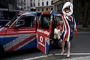 "The character known as Pandemonia is part-parody, a living sculpture and fine artist who is leaving a London Fashion show at Somerset House during London Fashion Week. Writing about herself at www.pandemonia99.com she writes that she is ""a 7ft tall personality often seen at exclusive premiers, events and exhibitions. Post pop, conceptual artist, written about in iD, independent and Vogue publications."" Otherwise, few have any idea about who or what this cartoon character is, or even how this creature secures an invite to parties, society and art events. The writer Poonperm Paitayawat says "".. She is about branding, self-image and lifestyle. She is tapping into the collective unconsciousness. Pandemonia goes beyond pop art.""bike."