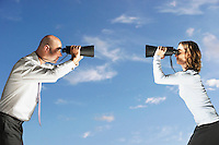 Business colleagues looking at each other through large binoculars outside profile