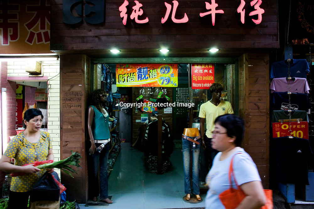 GUANGZHOU, 3. Mai , 2010:.ein Chinesin geht an einem Laden mit Schwarzen Mannequins  in der Naehe des Tianxiu Kaufhauses in Guangzhou vorbei...