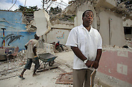 Romel Joseph, injured blind violinist, stands in front of The New Victorian School, destroyed from the earthquake that struck Haiti. He is looking forward to when he can teach again as workers clean up the site in preparation to rebuild the school on. Here he stands at the site on Wednesday June 23, 2010..***This is for Trenton Daniel story***.