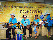 16 AUGUST 2015 - BANGKOK, THAILAND:  People sit in a bus shelter decorated with a royal advertisement on Phayathai Road at Victory Monument during the ''Ride for Mom'' in Bangkok. More than 100,000 people across Thailand participated in the Bike For Mom event in honor of Queen Sirikit, who celebrated her 83rd birthday August 12. In Bangkok, the ride was led by His Royal Highness Crown Prince Maha Vajiralongkorn, the Crown Prince of Thailand and Sirikit's only son. Queen Sirikit, who is in poor health and living in a hospital, was unable to attend the bike ride.    PHOTO BY JACK KURTZ