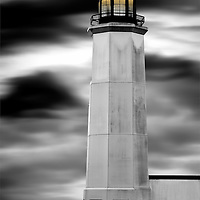 A lighthouse shines in the darkness of a rain front.