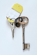 a small modern and big old key on a ring with a label