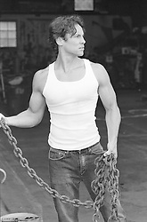 Muscular man in a tank t-shirt holding a large chain