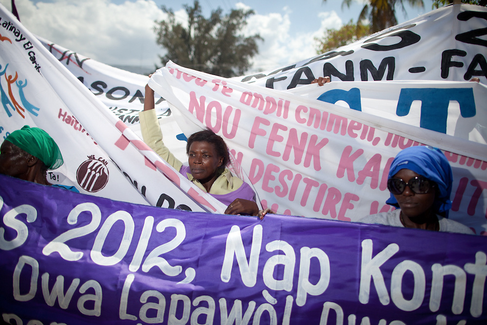 Women's groups arrange their protest banners when the march reaches the Haitian parliament. (Photo by Ben Depp)