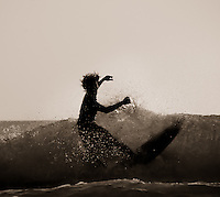 A Balinese surfer takes a final spin at the end of a ride, Kuta Beach, Bali, Indonesia, Southeast Asia.