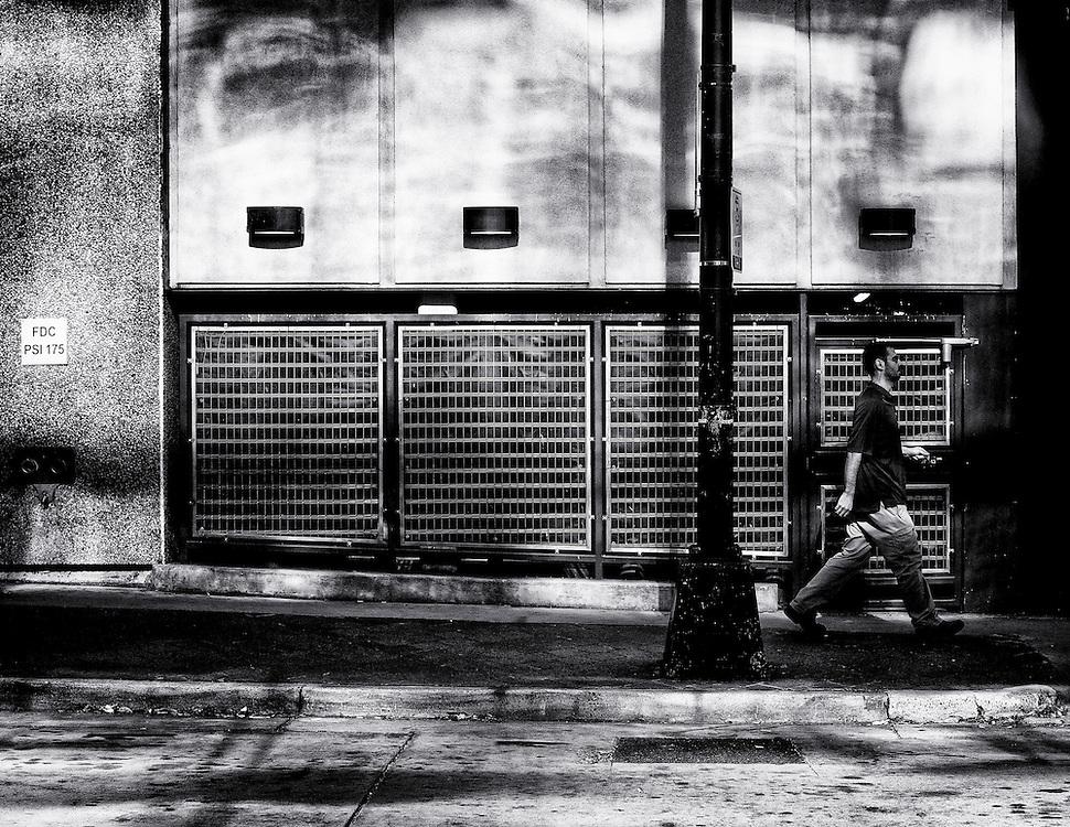 man walking down sidewalk with light and shadows