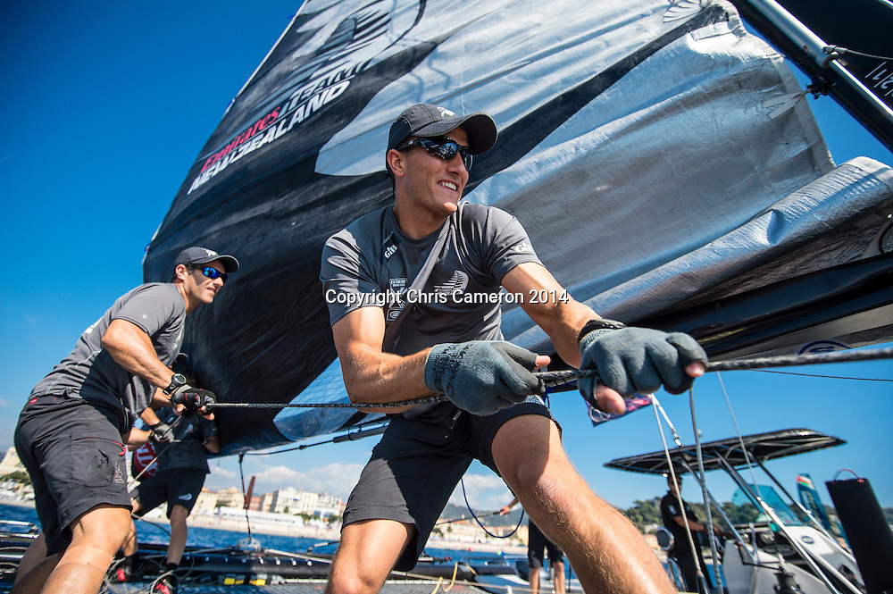 Emirates Team New Zealand sailors Jeremey Lomas and Blair Tuke haul the main sail up before racing on day two of the Extreme Sailing Series at Nice. 3/10/2014. Photo: Chris Cameron/www.photosport.co.nz