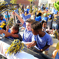 Thomas Street Elementary School students cheer and wave to the crowd as they ride in their float in the THS Homecoming Parade Thursday afternoon.