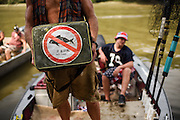 Carl Peiffer holds a seat cushion adorned with a no asian carp sticker at the 10th Annual Redneck Fishin' Tournament held Saturday, Sept. 5, 2015, in Bath, ILL. The only fishing tournament where poles are not allowed and you must catch the Asian Carp with a net or your hands as they fly through the air. This year 5,839 if the invasive species were removed from the Illinois River during the tournament. Photography by Rob Hart