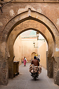 MARRAKESH, MOROCCO - 19TH APRIL 2016 - Local rides a motorbike stacked with leather hides through an arched doorway in the Marrakesh Medina, Morocco.