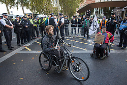 London, UK. 13 October, 2019. Disabled climate activists from Extinction Rebellion protest outside New Scotland Yard against tactics employed by police officers which impinge on the right to protest of disabled activists, including the confiscation of wheelchairs, wheelchair ramps, accessible toilets and tents. It was the seventh day of International Rebellion protests by Extinction Rebellion.
