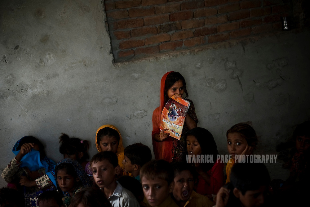 BASTI DIRKHAN WALA, PAKISTAN - JULY 14: A young student holds onto her exercise book during a class run by Tehmeena Fatima, 25, who opened a small school with the help of a cash grant, on July 15, 2011, in Basti Dirkhan Wala, Pakistan. Extreme poverty, poor diet and health, exposure to disease, and inadequate sanitation and hygiene annually produce alarming levels of malnutrition amongst children, but the floods of 2010 and 2011 have increasingly endangered an already vulnerable population. Child malnutrition has breached emergency levels in Pakistan - particularly Sindh province - after monsoon floods devastated the country's poorest region for a second year. Malnourishment It is the single biggest contributor to under-five mortality, increasing the risk of infections and slowing recovery from illness. It stuns both mental and physical growth and their future capacity, sapping the next generation's ability to meet the demands of a country already facing an unstable future. According to UN reports, hundreds of thousands of children in Pakistan suffer from severe-acute-malnutrition, with 15.1% of children experiencing acute malnourishment. The Economist recently reported that 44% of children in Pakistan suffer from varying degrees of malnutrition. (Photo by Warrick Page)
