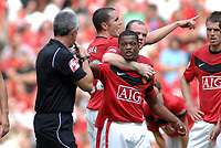Patrice Evra (Utd) is held back by Wayne Rooney after complaining to the Referee Mr Chris Foy after he was fouled before Chelsea'a 2nd goal. Manchester United v Chelsea FA Community Shield 2009 @ Wembley 09/08/2009  Credit : Colorsport / Andrew Cowie