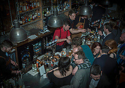 The world's best bartender, Jack McGarry, from New York (where he runs The Dead Rabbit bar, the best bar in the world 2016 ) is serving cocktails in Edinburgh this week. Here he is working in Devils Advocate just off the Royal Mile. All part of a five day Tales of the Cocktail event taking place in numerous venues across the city this week. Pictured: Jack McGarry (in red)<br /> <br /> <br /> © Jon Davey/ EEm