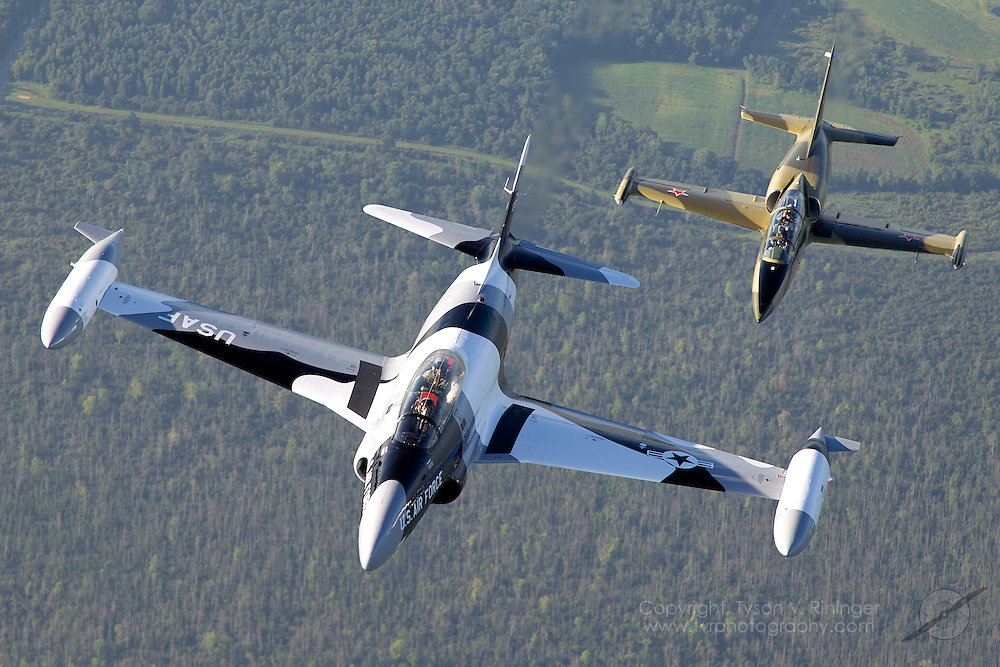 Paul Keppeler pilots a former Canadaire CT-133 Silver Star painted to resemble an arctic-camo T-33 Shooting Star over the Wisconsin countryside with Larry Labriola in close trail with his green camo L-39 Albatros.