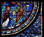 A resurrected Christ appears before Mary Magdalene in a garden, holding a cross and speaking Noli me tangere, the Resurrection of Christ, from the Life of Mary Magdalene stained glass window, 13th century, in the nave of Chartres cathedral, Eure-et-Loir, France. Chartres cathedral was built 1194-1250 and is a fine example of Gothic architecture. Most of its windows date from 1205-40 although a few earlier 12th century examples are also intact. It was declared a UNESCO World Heritage Site in 1979. Picture by Manuel Cohen