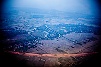 An aerial view over northern Vietnam showing a winding river, small villages, and rice fields in the late afternoon.