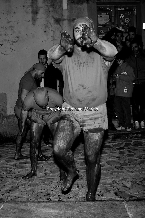 "Verbicaro/Calabria/Italy 20-03-08 - Ritual of the ""Battenti"". On the night of Holy Thursday Verbicaro stages the traditional rite of Battenti, which dates back to 1473. Initially characterized by ""the rite of the first blood"", which means the protagonists beat their legs vigorously with their hands until they become red. Then, with a tool cork ""cardillo"" which has embedded pieces of glass, they start to beat themselves and the first blood flows. As the blood flows, a man carrying a bottle to his lips, blows wine into the wounds...When everyone has his legs covered with blood, they start to run with hands crossed on the chest. Three times they circle the old town stopping in front of churches. They leave as a group but it is not a procession, each runner has their own route and the streets may differ. The event takes place between Thursday  and Friday  (between midnight and 02.00). At 4.00 (approx.) in the morning there is a solemn procession with living statues and paintings."
