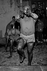 """Verbicaro/Calabria/Italy 20-03-08 - Ritual of the """"Battenti"""". On the night of Holy Thursday Verbicaro stages the traditional rite of Battenti, which dates back to 1473. Initially characterized by """"the rite of the first blood"""", which means the protagonists beat their legs vigorously with their hands until they become red. Then, with a tool cork """"cardillo"""" which has embedded pieces of glass, they start to beat themselves and the first blood flows. As the blood flows, a man carrying a bottle to his lips, blows wine into the wounds...When everyone has his legs covered with blood, they start to run with hands crossed on the chest. Three times they circle the old town stopping in front of churches. They leave as a group but it is not a procession, each runner has their own route and the streets may differ. The event takes place between Thursday  and Friday  (between midnight and 02.00). At 4.00 (approx.) in the morning there is a solemn procession with living statues and paintings."""