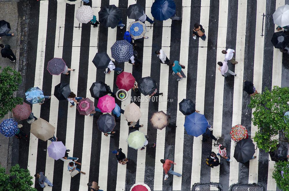 Pedestres atravessando a rua durante a chuva./ Pedestrians crossing the road during rain. Brasil, 2013
