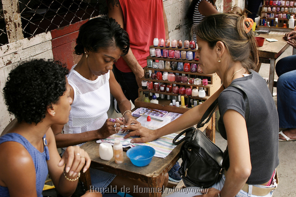 Manicure on a small market in Santiago de Cuba. This is one of the few jobs that are allowed to be exercised privately in Cuba, so it is offered almost anywhere in every street.