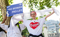 © Licensed to London News Pictures. 10/06/2018. London, UK. Pro-life and pro-choice protesters stand by the Millicent Fawcett statue in Parliament Square after thousands of people marched through central London wearing green, white and violet, the colours of the Suffragette movement,  to celebrate 100 years votes for women. Photo credit: Rob Pinney/LNP