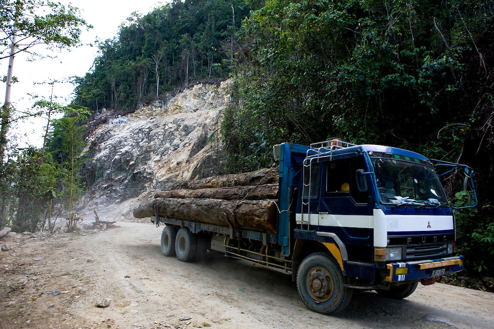 A log truck drives past the site of where the Indonesian military uses explosives to clear rocks on the site of the future Trans Papuan Highway near the village of Beniek, Indonesia, Sept. 4, 2008..Daniel Beltra/Greenpeace
