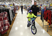 Leo Taylor tries out his new bicycle with Gary Police Lt. Tom Ruzga  during the Gary FOP Lodge 61 and Gary Police Department Toys for Kids event Saturday at Meijer in Merrillville.
