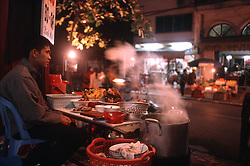 Color film photograph of vender sitting at his street food shop at night waiting to serve customers Pho, the traditional Vietnamese soup, Truc Bach, Hanoi, Vietnam