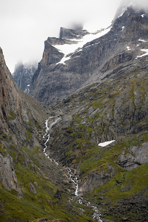 Greenland, Frederiksdal, Glacial stream flows through jagged mountains at end of Narsap Sarqaa fjord  on summer evening