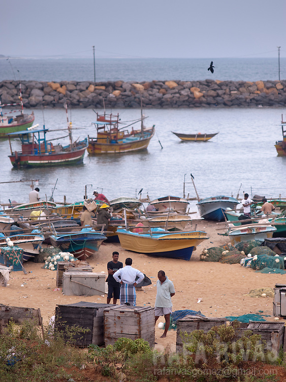 Men stand next o fishing boats at the Hanbantota sea-port, in Sri Lanka, on February 26, 2011