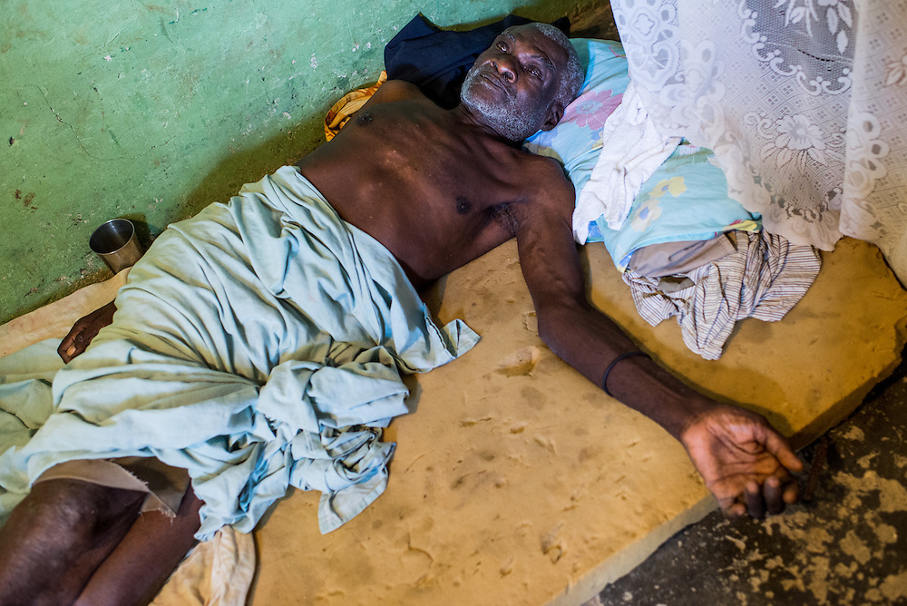 A sick elderly man lies on a mattress on the floor of his daughter's one-room shack in Batey Ocadulna, Jan. 5, 2014. With no accessible transportation aside from motorbikes, even if a family can afford medical treatment for loved ones, transporting the sick or elderly to distant hospitals proves a significant problem.