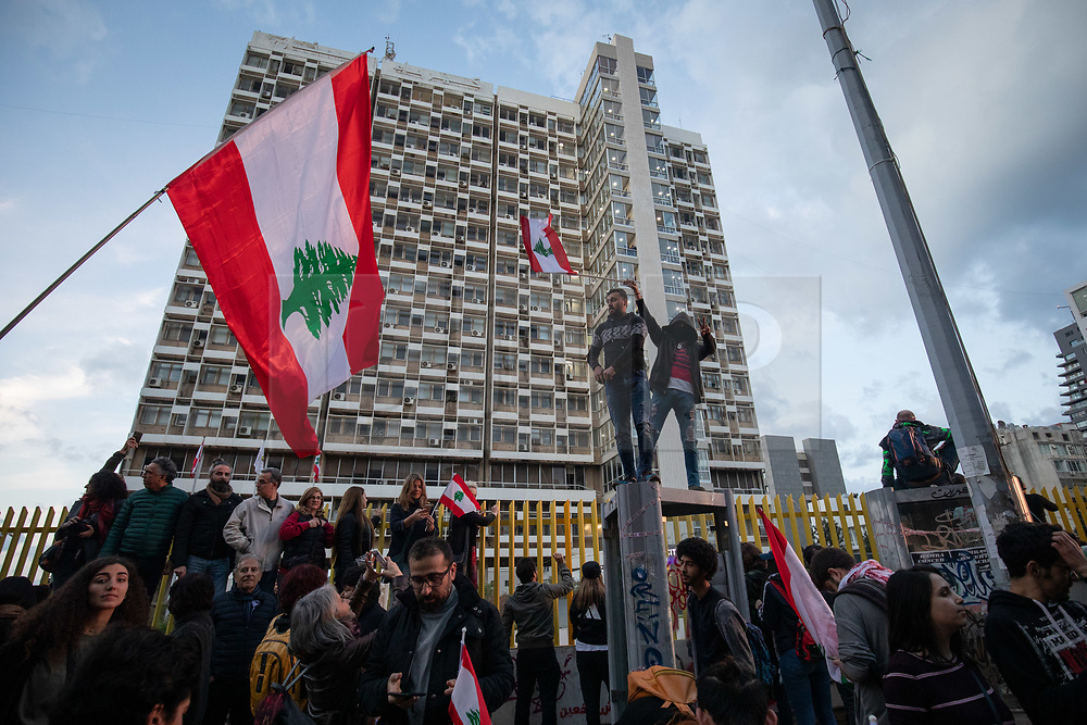 ©2020 Tom Nicholson. 11/01/2020. Beirut, Lebanon. People wave the Lebanese flag outside 'Electricité du Liban', the main Lebanese electricity provider. Demonstrators are taking part in a protest march from Daoura in east Beirut to Parliament in Downtown Beirut. The demonstrations are part of a wider movement which started in mid October 2019, campaigning against government corruption and economic crisis. Photo credit : Tom Nicholson