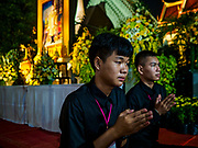 25 OCTOBER 2017 - BANGKOK, THAILAND: Teenagers pray for the late king in front of a portrait of the late king during the funeral for Bhumibol Adulyadej, the Late King of Thailand. He died in October 2016 and was cremated during an ornate five day funeral on 26 October 2017. He reigned for 70 years and was Thailand's longest serving monarch.         PHOTO BY JACK KURTZ