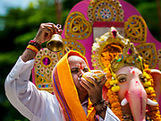 "23 SEPTEMBER 2018 - BANGKOK, THAILAND:  A man rings a bell and blows a prayer conch to honor Ganesha at the Ganesha Festival at Wat Dan in Bangkok. Ganesha Chaturthi also known as Vinayaka Chaturthi, is the Hindu festival celebrated on the day of the re-birth of Lord Ganesha, the son of Shiva and Parvati. The festival, also known as Ganeshotsav (""festival of Ganesha"") is observed in the Hindu calendar month of Bhaadrapada, starting on the the fourth day of the waxing moon. The festival lasts for 10 days, ending on the fourteenth day of the waxing moon. Outside India, it is celebrated widely in Nepal and by Hindus in the United States, Canada, Mauritius, Singapore, Thailand, Cambodia, and Burma.   PHOTO BY JACK KURTZ"