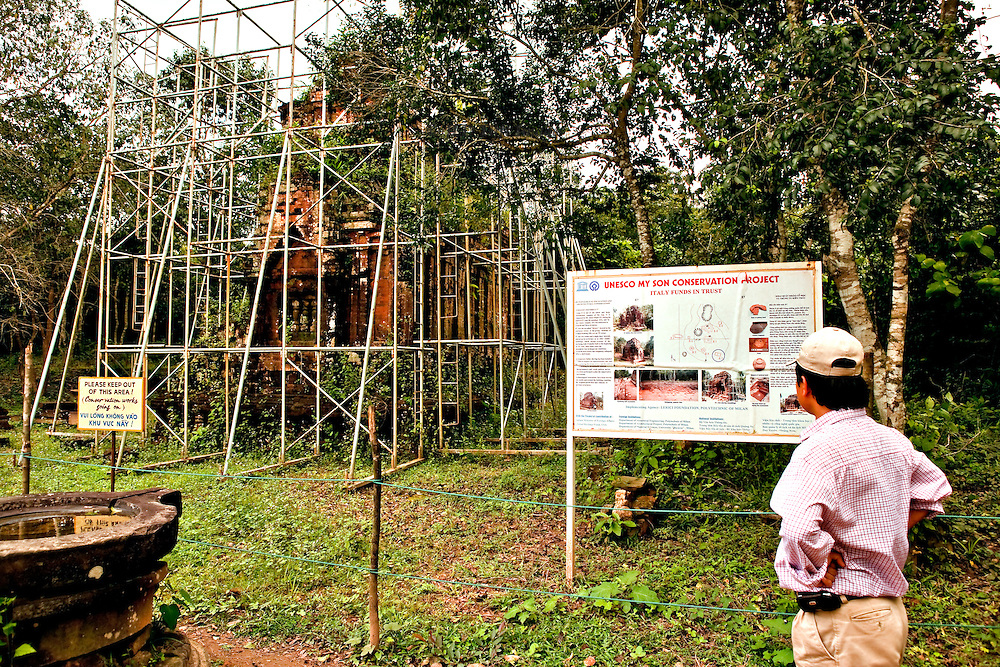 A Temple to Shiva with light scaffolding around it and a billboard examined by a male visitor: Italian-funded UNESCO conservation works in progress.