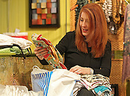 Owner Heidi Sills sorts through incoming clothes at Crazy Daisy, 712 3rd Avenue SE in Cedar Rapids on Friday, December 16, 2011. (Stephen Mally/Freelance)