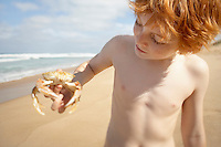 Boy holding crab on beach portrait