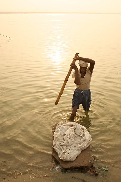 """A clothes washerman (A Dhobi Wallah) washeds clothes along the Ganges River in Varanasi, India. The word dhobi comes from the Hindi word """"dhona,"""" which means, """"to wash."""""""