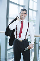 Businessman smiling and looking at camera with jacket over shoulder