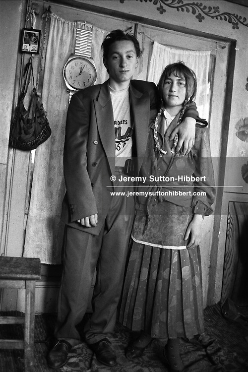 Bratu Mihai puts his arm around his friends wife, Zambila Mihai. Bratu Mihai also wears a pager on his belt, even though this does not work, it is worn a sa status symbol. They live in the Kalderash Roma camp of Sintesti, near Bucharest.