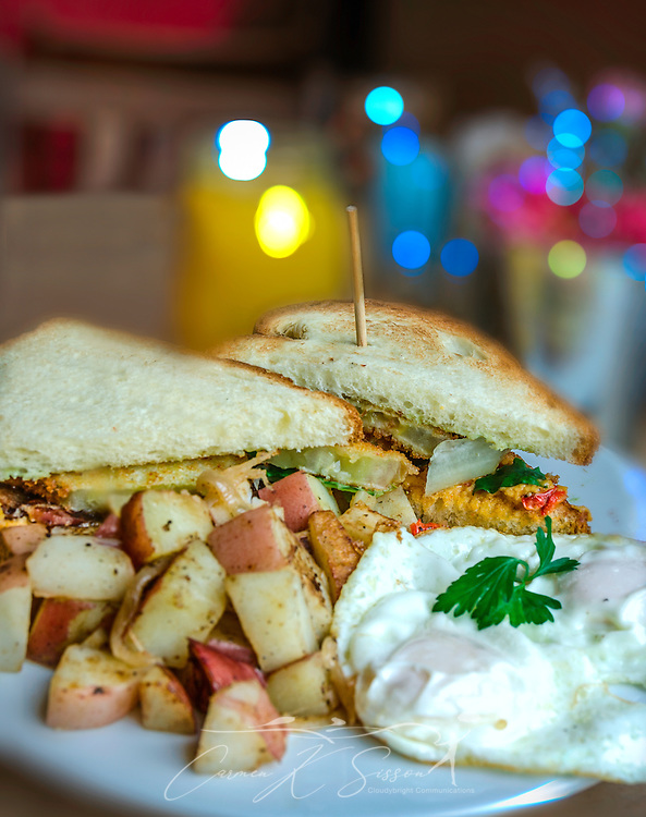 A P.B.L.T. sandwich, containing pimiento cheese, fried green tomatoes, bacon, and scallion aioli, is served with red potatoes at Sun in My Belly Cafe, June 15, 2014, in the Kirkwood community of Atlanta, Georgia. The cafe, founded in 1996 by master chef Alison Lueker, specializes in local and seasonal food with an elegant flair. The restaurant is housed within the historic Bailey's Hardware building. (Photo by Carmen K. Sisson/Cloudybright)