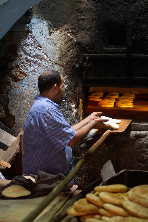 FEZ, MOROCCO - 25th OCTOBER 2013 - Baker prepares bread at a ferrane (communal oven) bakery in the old Fez Medina, Middle Atlas Mountains, Morocco.