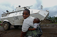 Kiwanja, Congo - A woman and her baby pass by a U.N. tank  at a camp for displaced people in this rebel-held town. U.N. peacekeepers have been unable to protect more than 250,000 civilians who've fled a recent CNDP rebel advance across Eastern Congo. (Photo by Miguel Juarez Lugo)