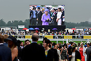 © London News Pictures. 20/06/2013. Ascot, UK. Her Majesty Queen Elizabeth projected on a large screen overlooking the racecourse. Ladies Day on day three of Royal Ascot at Ascot racecourse in Berkshire, on June 20, 2013. The 5 day showcase event, which is one of the highlights of the racing calendar, has been held at the famous Berkshire course since 1711 and tradition is a hallmark of the meeting. Top hats and tails remain compulsory in parts of the course.  Photo credit : Stephen Simpson/LNP