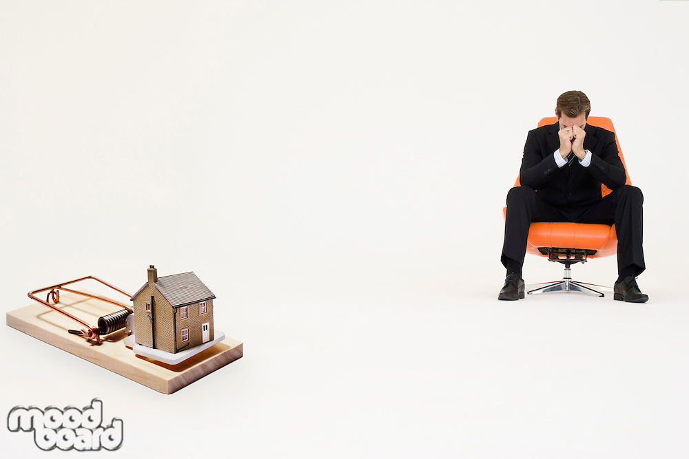 Model home on mouse trap with worried businessman sitting on chair representing increasing real estate rates