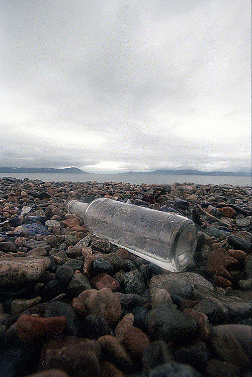 039078.AA.0820.warming22.kc--Bering Sea, Off Providenya, Russia--An empty Vodka bottle sitws on the rocks along the shore. The story deals with the enviromental issue of global warming throughout the region of Russia directly across the Bering Sea from Nome, Alaska. The story touches on the people their way of living, the rough economy and the extent they are effected by the slowly warming temperature as documented by scientists.  More Details To Come.