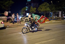 © Licensed to London News Pictures. 27/04/2014. Sulaimaniya, Iraq. Two young men fly the flag of the Patriotic Union of Kurdistan (PUK) political party and a flag bearing the face of Abdullah Öcalan, the leader of the PKK a Kurdish militant organisation that fights for Kurdish rights in Turkey, during celebrations in the lead up to the 2014 Iraqi parliamentary elections in Sulaimaniya, Iraqi-Kurdistan.<br /> <br /> Although banned in other parts of Iraqi-Kurdistan, the days leading up to an election in Sulaimaniya sees political supporters of all the three main parties parading up and down the main street of the city, waving flags, honking horns, letting off fireworks and firing pistols and rifles into the air.<br /> <br /> The period leading up to the elections, the fourth held since the 2003 coalition forces invasion, has already seen six polling stations in central Iraq hit by suicide bombers causing at least 27 deaths. Photo credit: Matt Cetti-Roberts/LNP